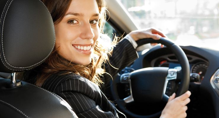 Young businesswoman looking at camera and smiling in a car